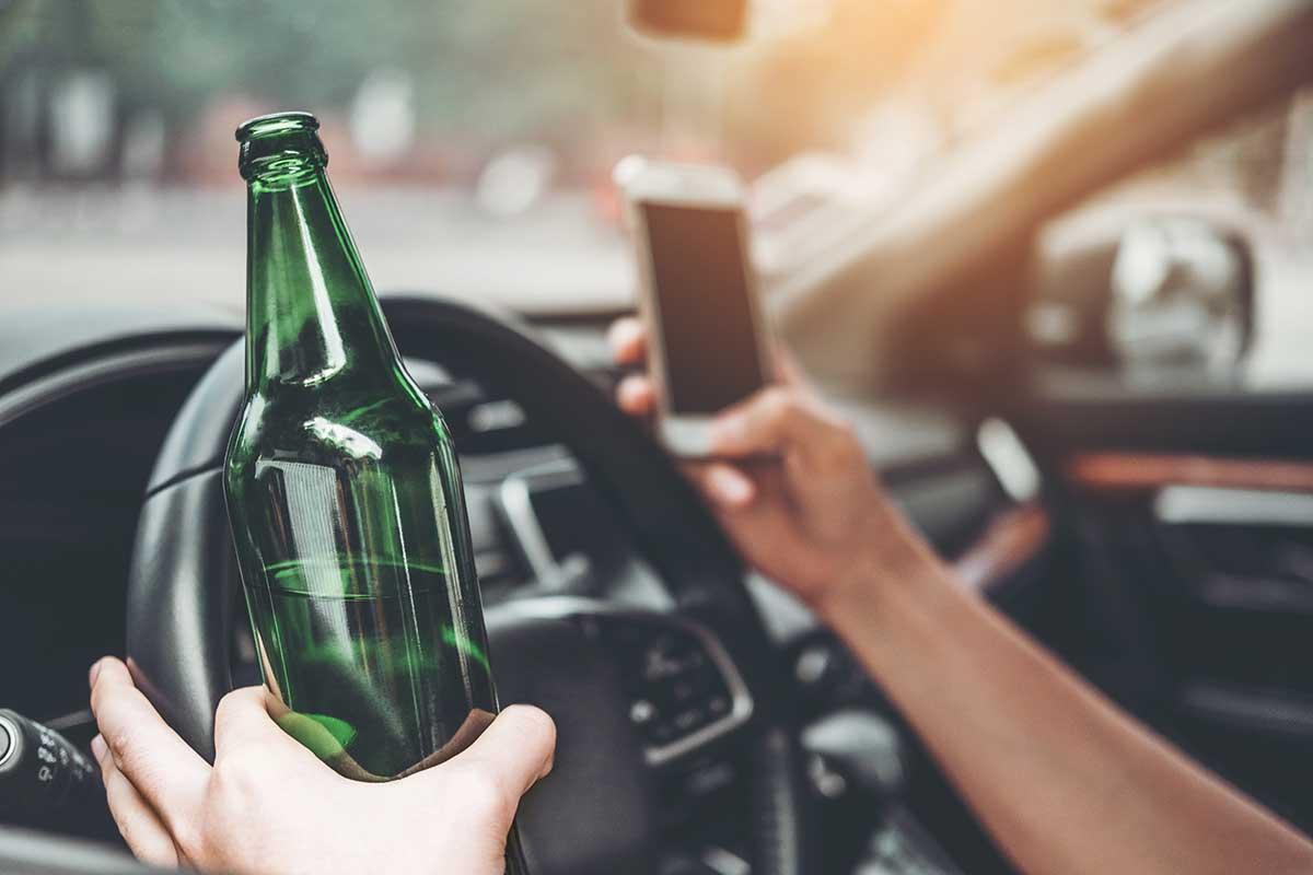 Bild von Fachgebietsseite Verkehrsrecht. Mann sitzt im Auto mit Smartphone und Bierflasche